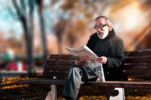 Older gentleman reading newspaper on the bench